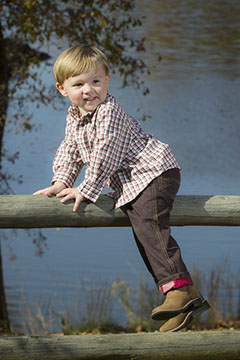 A handsome boy on a fence at Tuscaloosa's Riverwalk. Taken by a Tuscaloosa children's photographer.