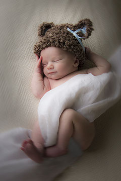 Tuscaloosa, Alabama baby photographer picture of cute baby wrapped in cloth with a hat.