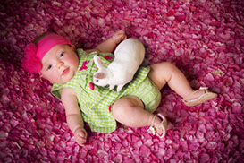 Adorable baby girl on a bed of flowers with a live bunny. Taken by a Tuscaloosa, Alabama baby photographer.