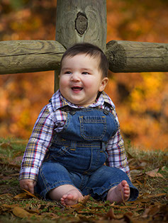Tuscaloosa photographer picture of a baby in overalls against a fence with beautiful fall colors.