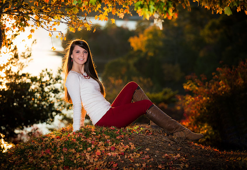 Fall senior picture with beautiful fall colors of leaves changing colors.
