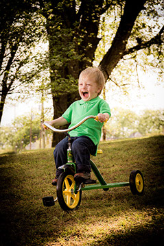 Tuscaloosa photographer picture of a boy riding his tricycle down a grassy hill.