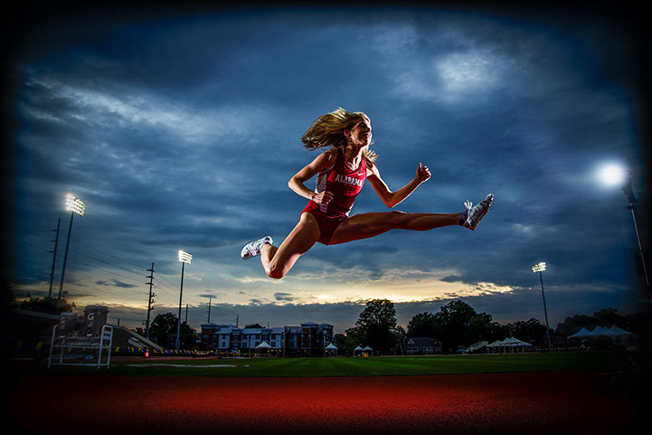 University of Alabama Graduation Pictures of a track and field athlete in her Alabama Track uniform leaping it the track lights at dusk.